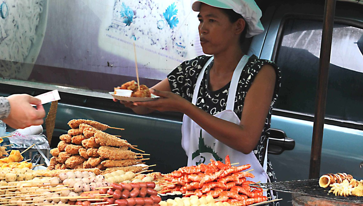 Today the boats have been replaced by stalls. Here a street vendor in Bangkok sells a variety of skewers of meat and sea food