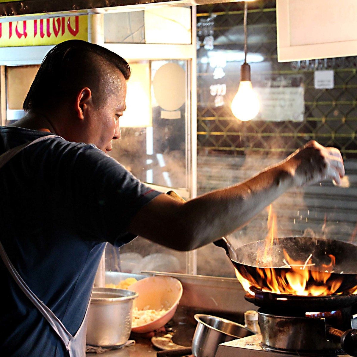 Cooking over a wok in a Bangkok night market. I wonder how many of these stalls go up in flames? Probably not many - the chefs know what they're doing