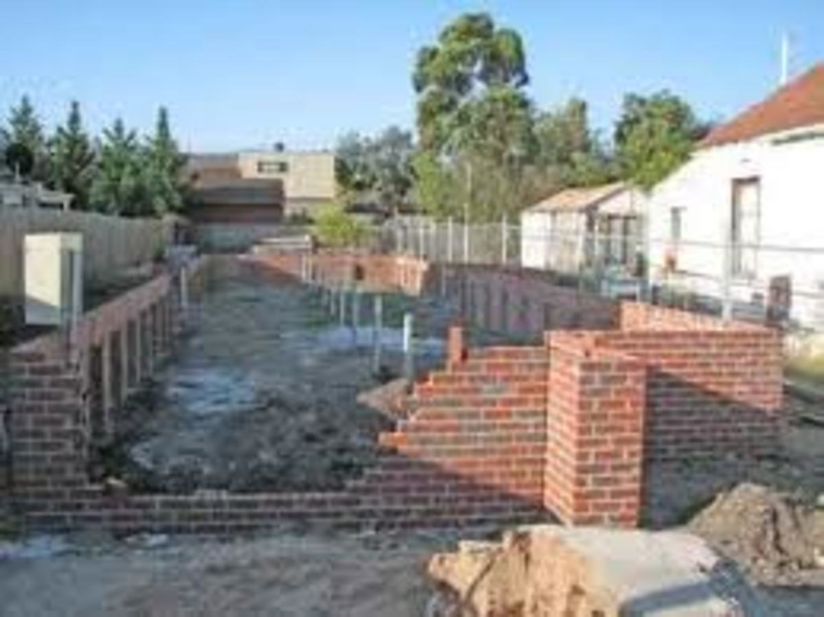 A house brick base and columns for a long and narrow house under construction.