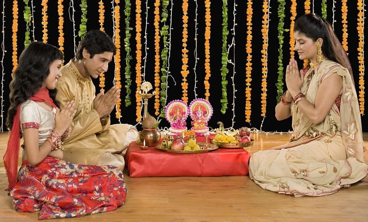 Family performing Lakshmi puja at home.