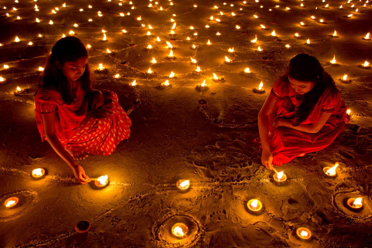 Girls in traditional dresses lighting diyas