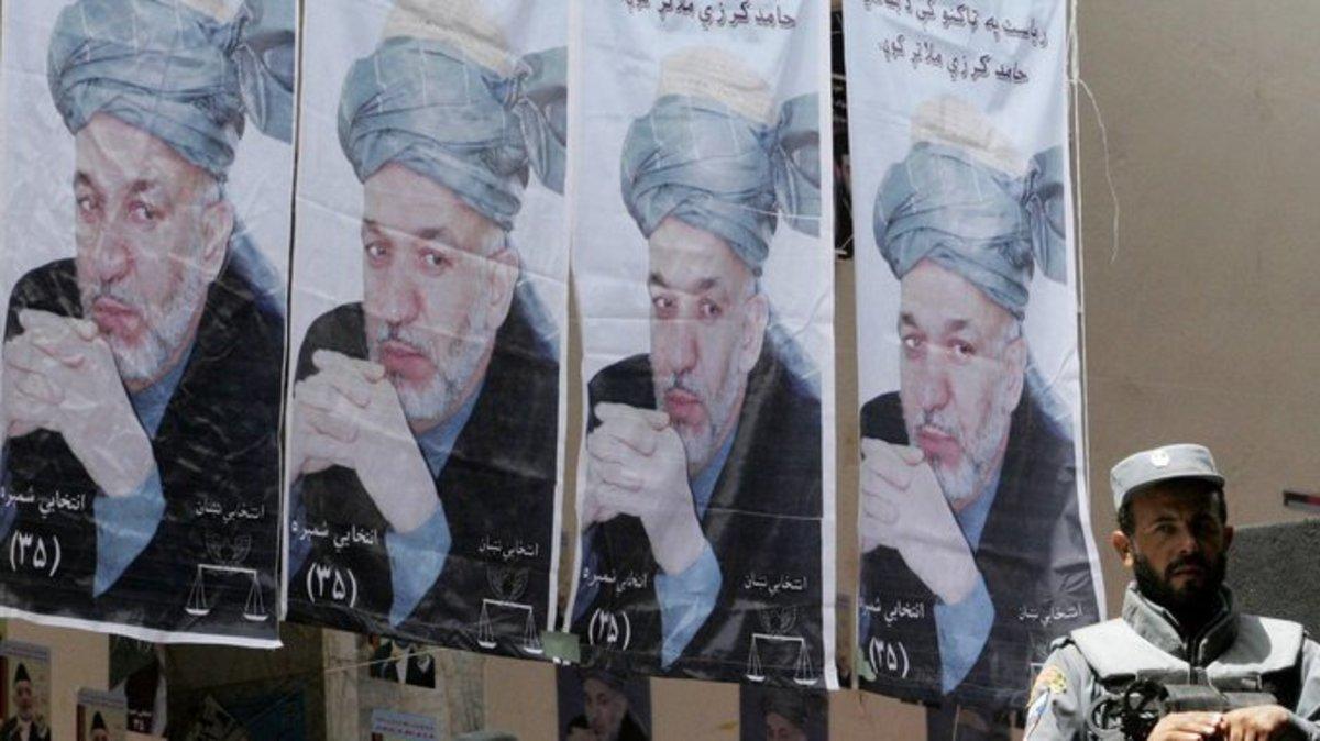An Afghan policeman with campaign photos of Hamid Karzai. Allauddin Khan/AP Images