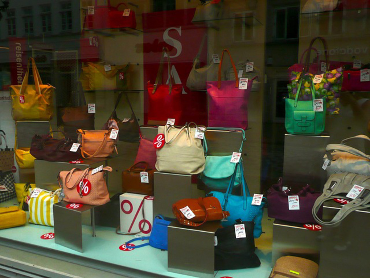 An arrangement of colorful handbags on individual display stands in the front window of a retail store.