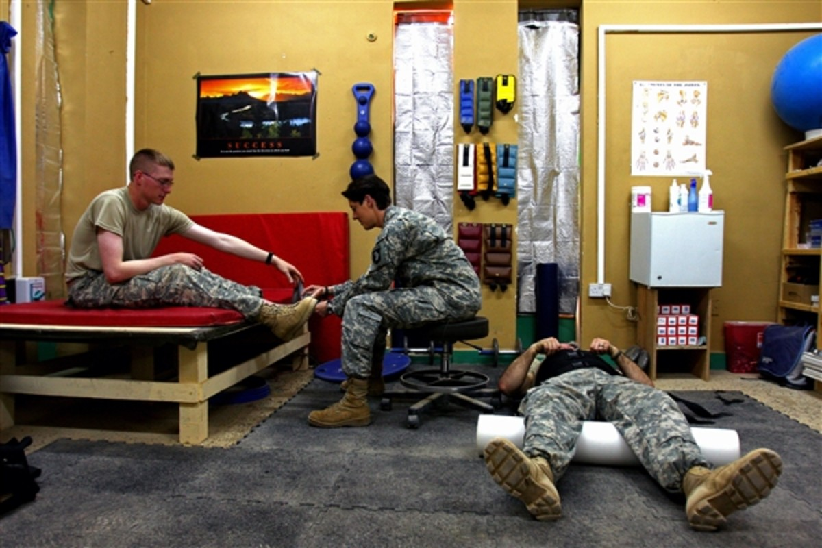 Army Staff Sgt. Gaither, physical therapy noncommissioned officer in charge with 1st Brigade Combat Team, 101st Airborne Division, checks on a soldier with back pain at the combat support hospital at Contingency Operating Base Speicher, Iraq.