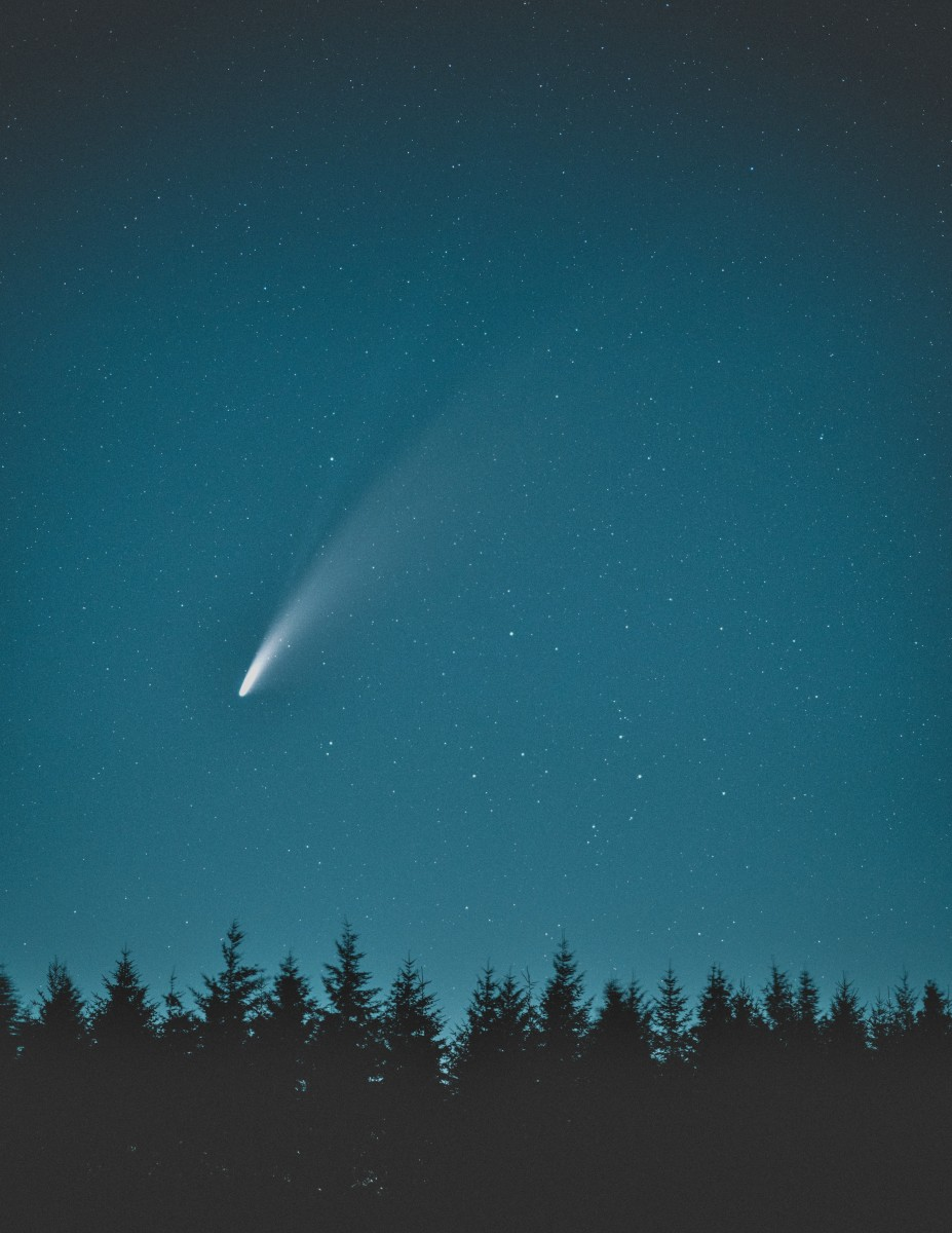 A falling star shoots downward from the night sky.