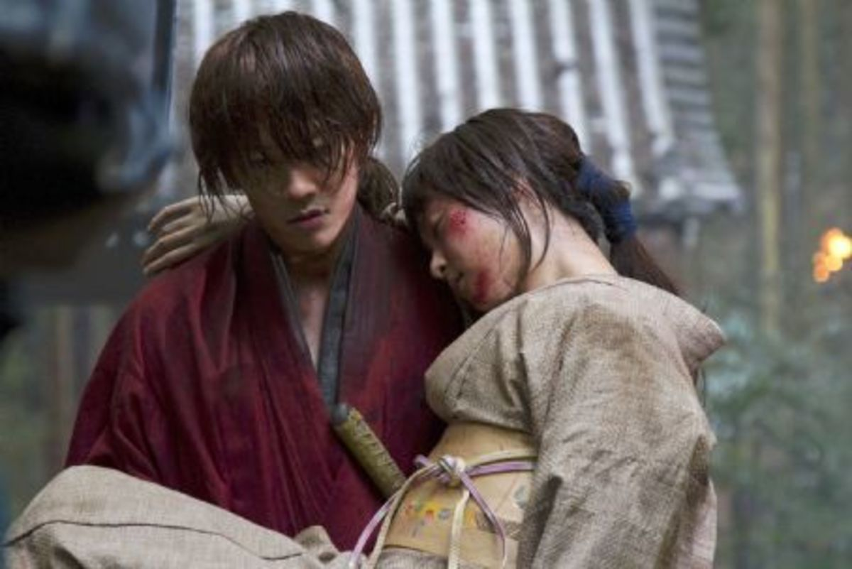 Courtesy of Netflix and Warner Bros. A wounded Kaoru being carried to safety by Kenshin, who at this time is about 28.