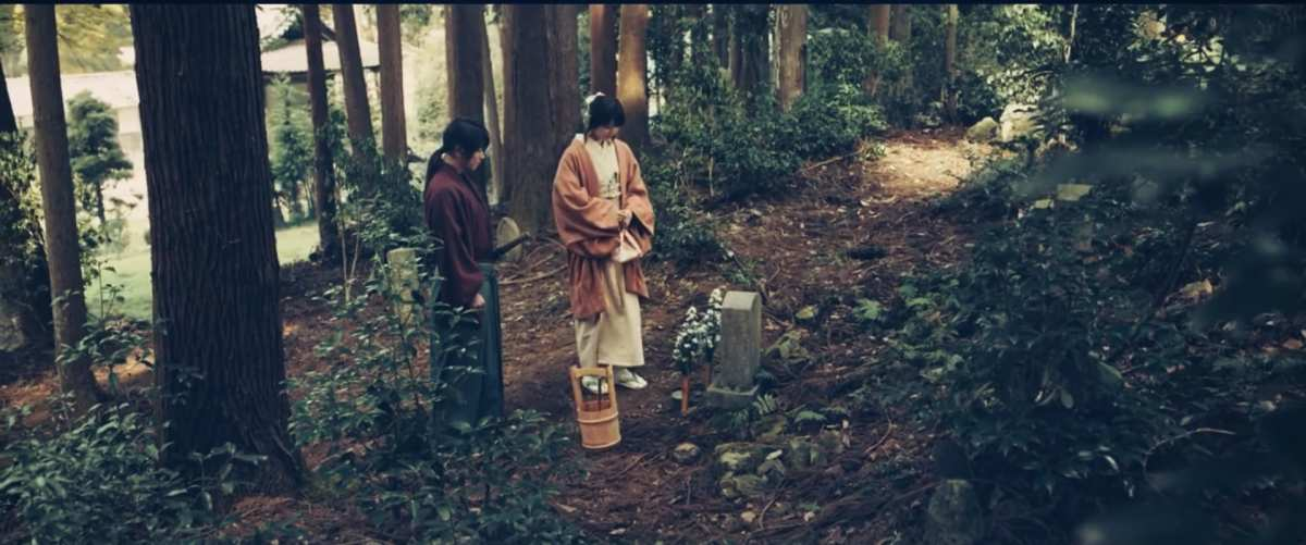 Courtesy of Netflix and Warner Bros. Kenshin and Kaoru visit Tomoe's grave stone near Kyoto in Rurouni Kenshin: The Final.