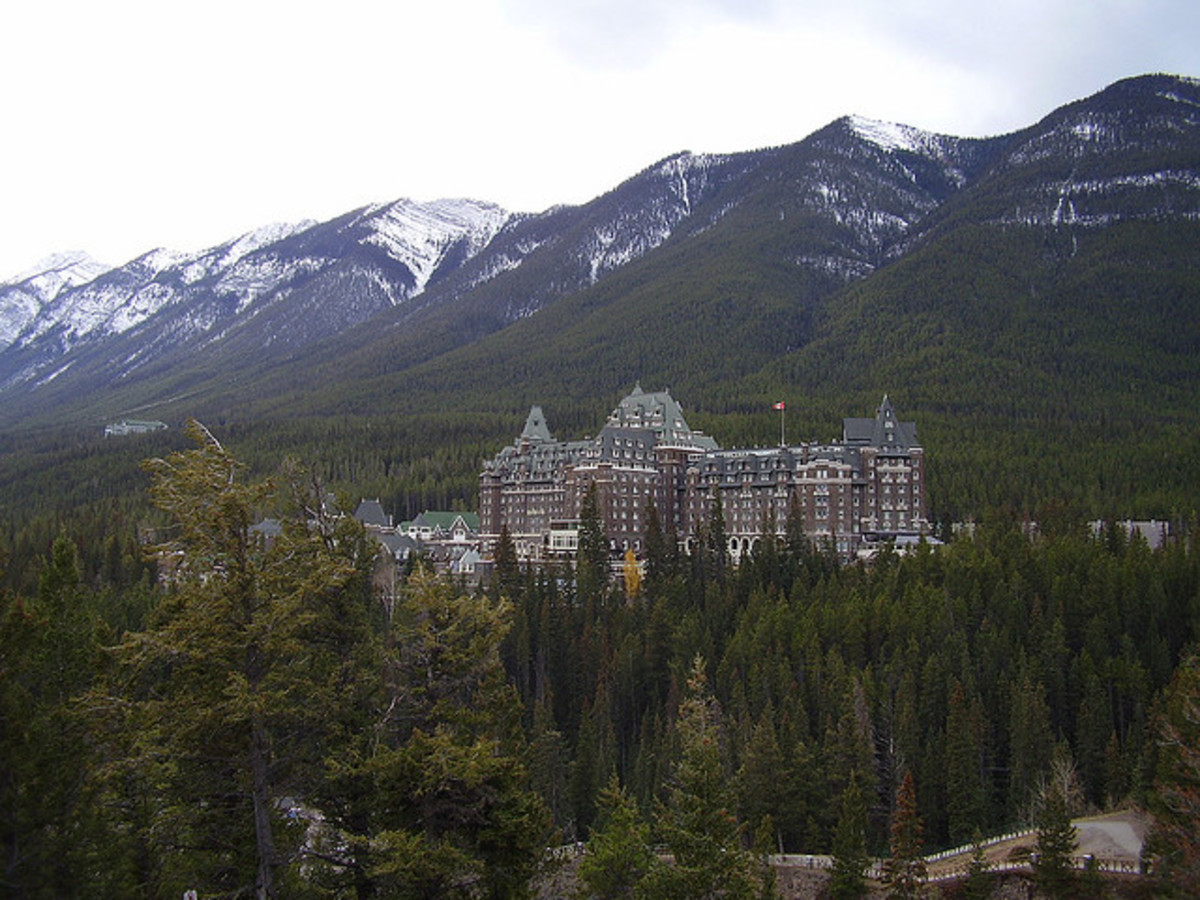 A distant shot of the Fairmont Banff Springs Hotel nestled into the Rocky Mountains.