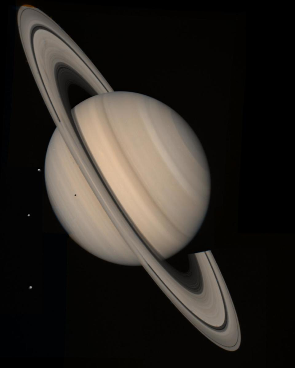The ringed planet Saturn, (and several of its moons) photographed by Voyager 2