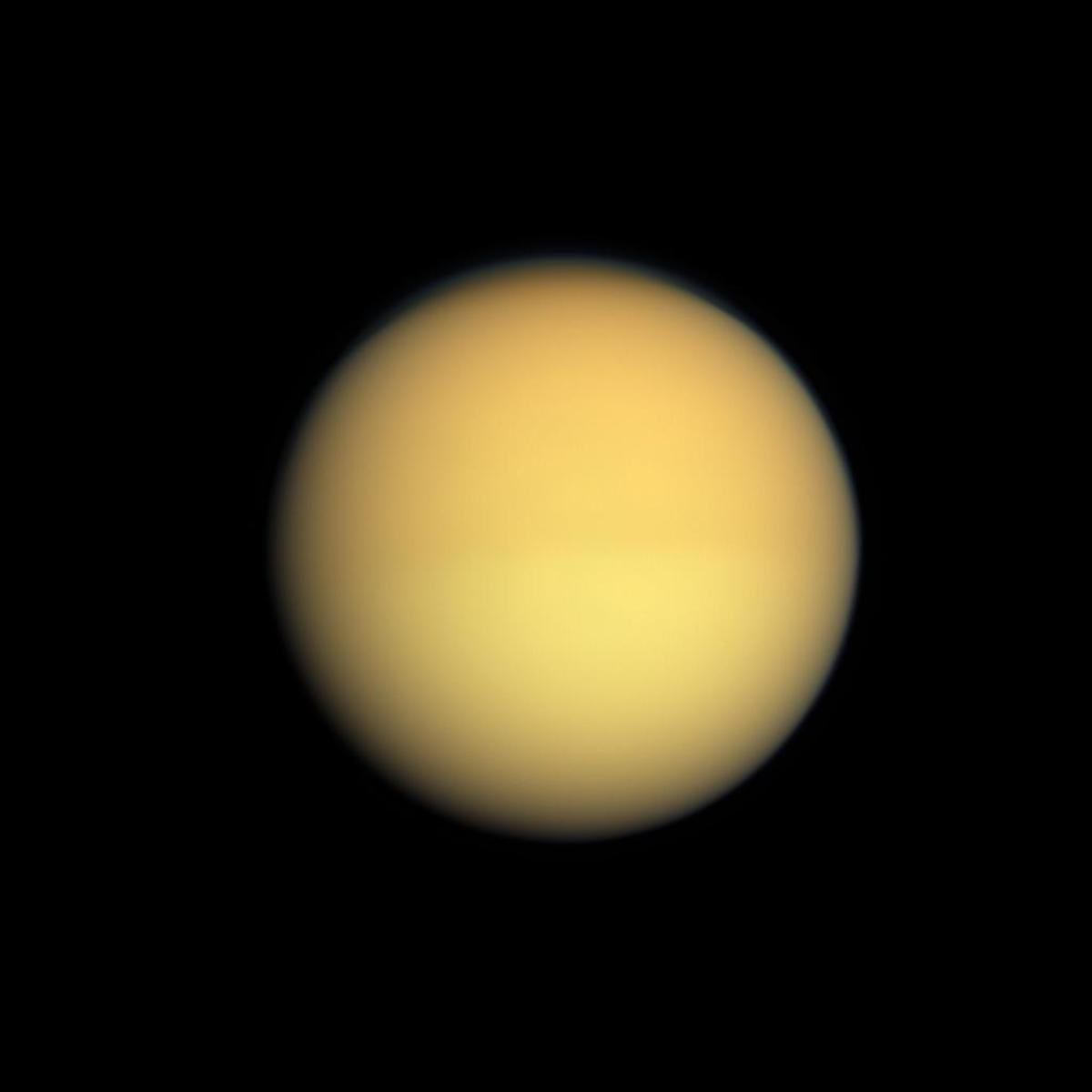 The strange moon Titan. The photo isn't blurred - the fuzziness is caused by the thick atmosphere which shrouds the surface of Titan and which is impenetrable to any attempts at imaging from space