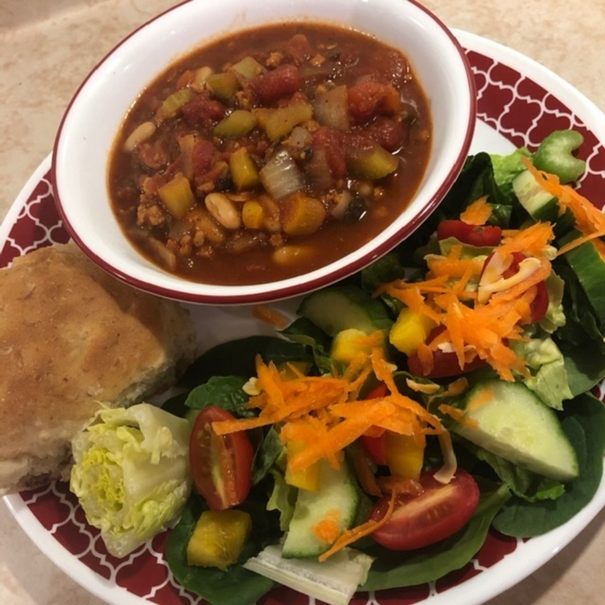 Vegan chili served with salad and homemade bread rolls
