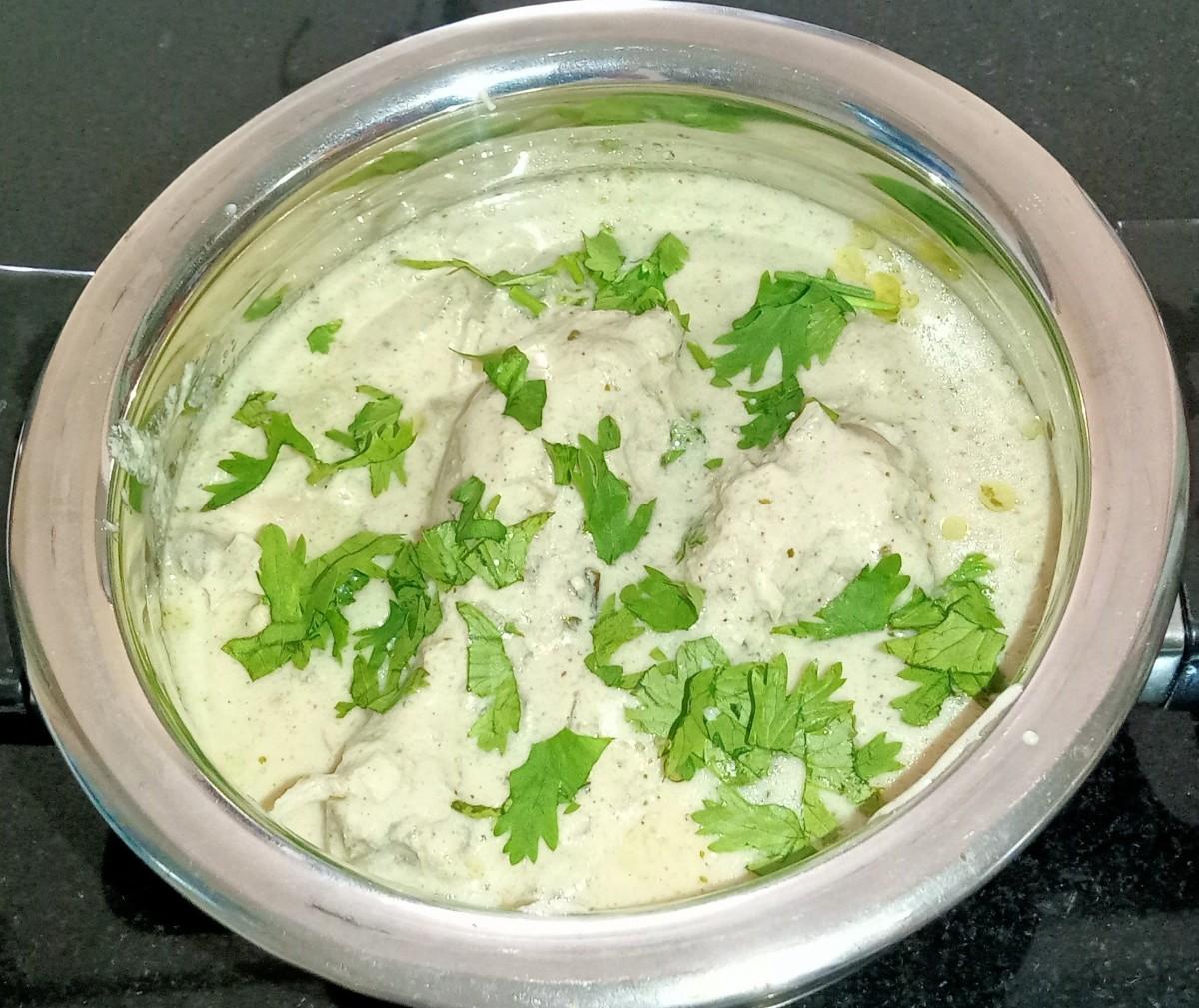 Chicken malai handi garnished with coriander leaves