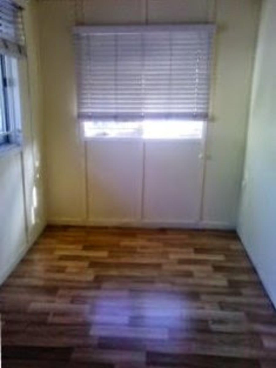 This is a veranda or patio that has been enclosed and now it cuold be used as a small room.