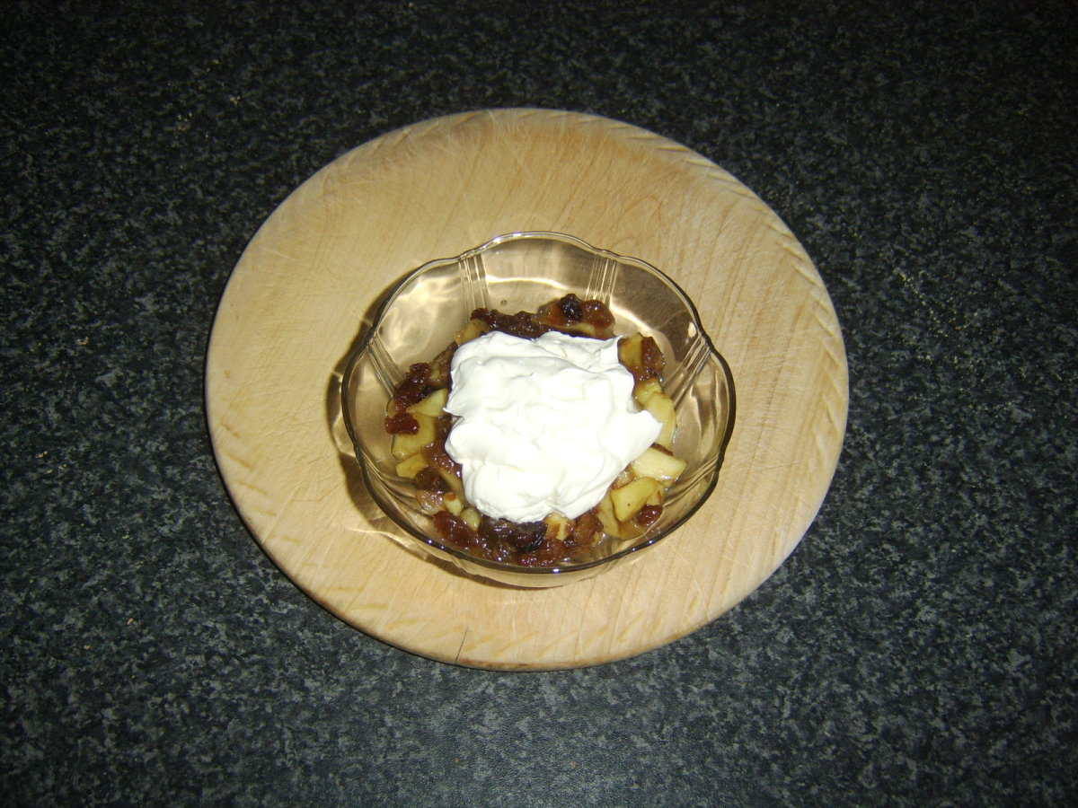 Whipped cream is added to the top of apples, sultanas and mincemeat