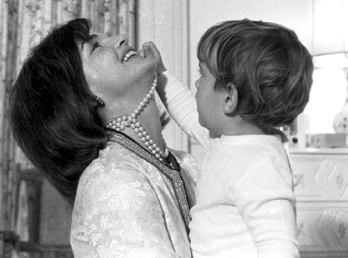 Photo of Jackie Kennedy with JFK Jr playing with her pearl necklace