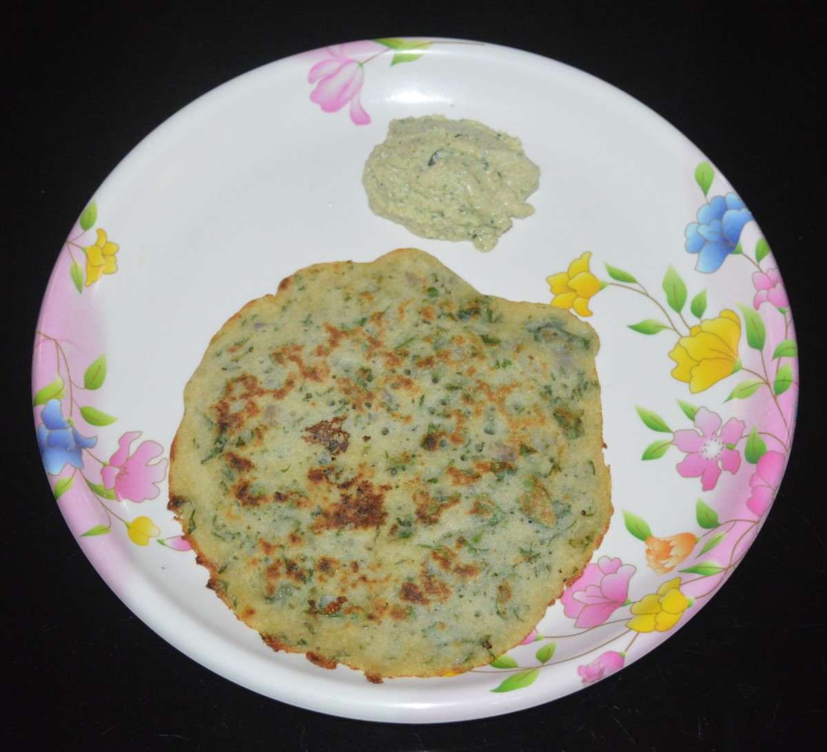 When the edges become golden brown, flip it. Add some oil or ghee to the top. Allow the bottom side also cook nicely and get golden brown spots. Remove and place it on a plate. Serve hot with coconut chutney. Enjoy!