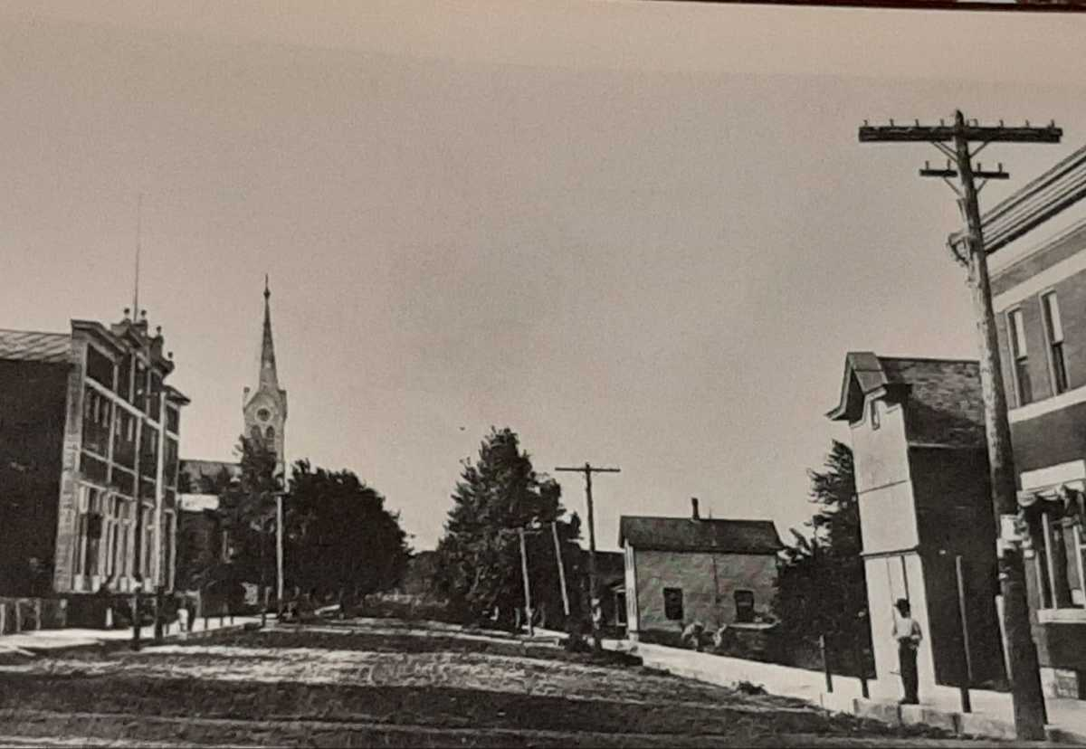 Spire of Saint Thomas Aquinas Church seen on left looking from Main Street down River Road.  Picture taken in early 1900s.